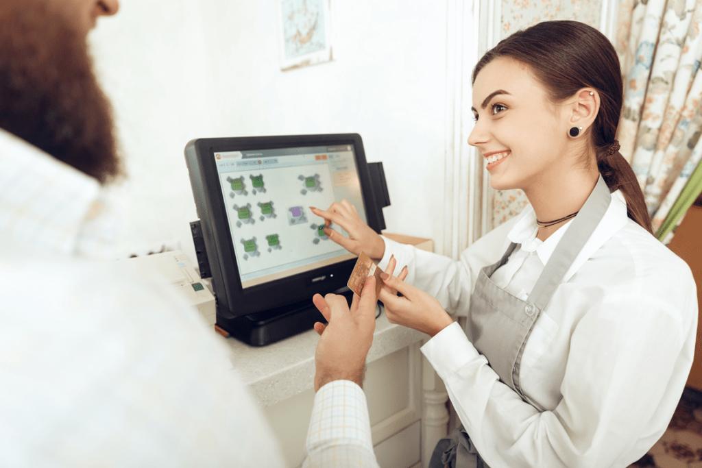 Commerçante prenant la carte fidélité d'un client